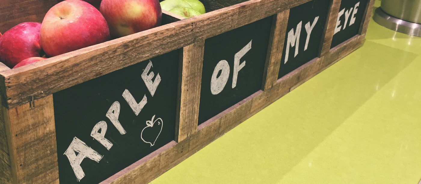 "Wooden crates on a table, filled with apples. On the front is written ""Apple of my eye"""