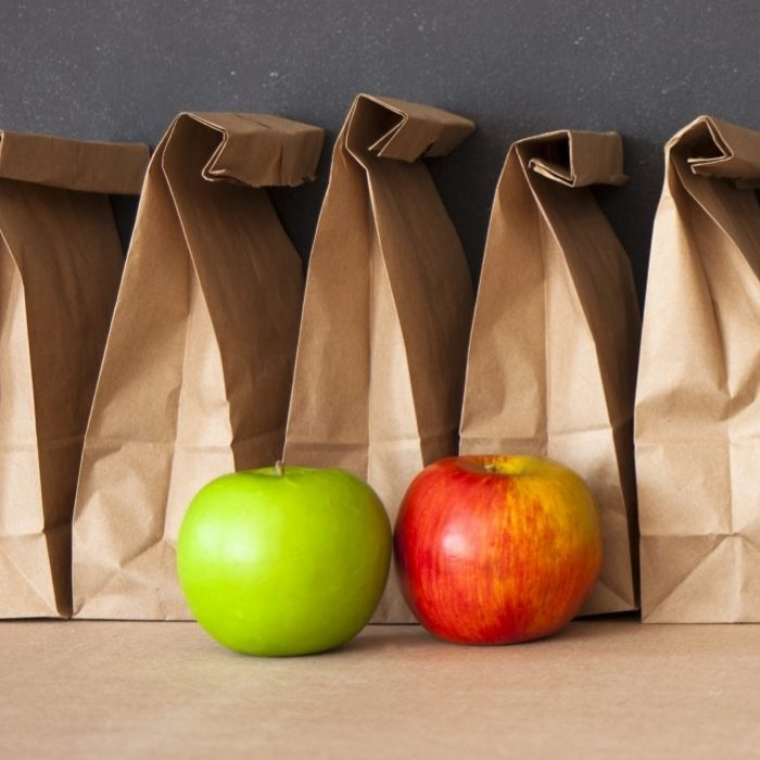 Five brown bags for lunch with apples